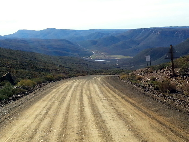 Gravel road leading into a valley