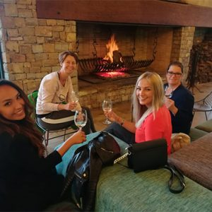 Guests drinking wine at fireplace